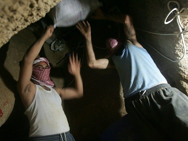 asked Palestinian men smuggle food, milk and supplies as they work underground June 27, 2008 in a tunnel, which links between Rafah southern Gaza Strip and Egypt.