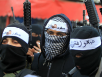Palestinian members of Al-Aqsa Martyrs' Brigades, the armed wing of the Fatah movement, raise their weapons during a rally to support Palestinian president and his government on March 1, 2016 in the West Bank Balata refugee camp near Nablus