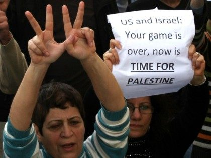 Palestinians hold signs as they rally in the centre of the West Bank city of Ramallah demanding an end to the split between the Gaza Strip and the West Bank and calling for political reconciliation between the Fatah party and the Islamist movement Fatah, on February 24, 2011.