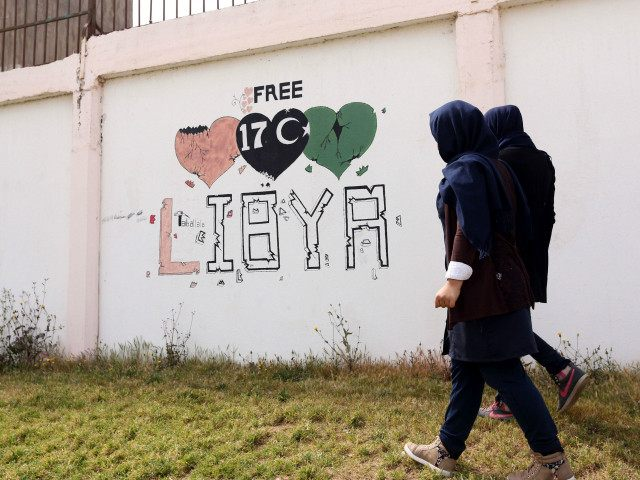 "LIBYA, Tripoli : Students walk past a wall painted with a graffiti reading ""free Libya"" in the Libyan capital Tripoli, on March 31, 2016. / AFP / MAHMUD TURKIA"