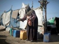 A Palestinian Bedouin woman washes a bowl on October 22, 2013 at an encampment where she lives with her family in tents amid harsh living conditions with no electricity in southern Gaza City.