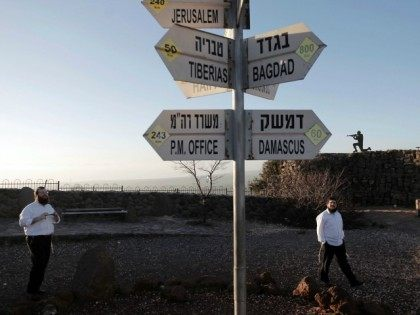 Israelis walk near a sign for tourists showing the distance to Damascus and Baghdad among other destinations at an army post on Mount Bental in the Israeli-annexed Golan Heights on March 10, 2016. Israel and Syria have formally been at war for decades though the demarcation line between them had …