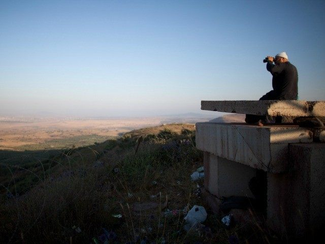 A Druze man looks at the nearby Syrian village of Jebata al-Khashabn from an Israeli army post near the village of Buqaata at the Israeli side of the border on July 24, 2012 in the Golan Heights.