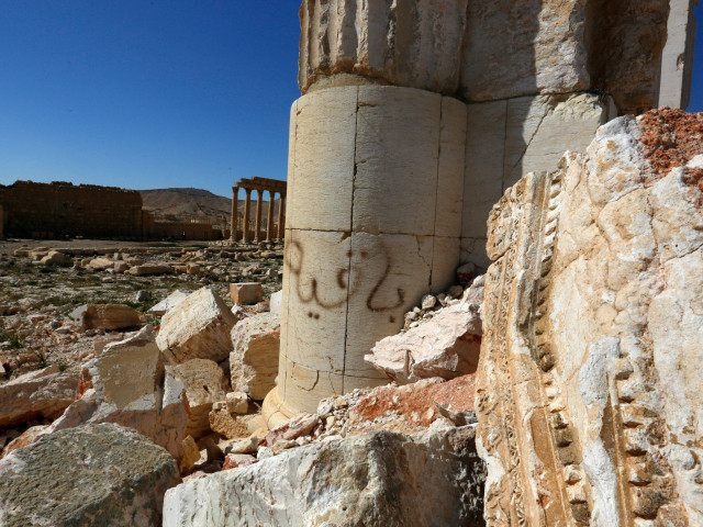 In this picture taken Friday, April 1, 2016, graffiti and damage are seen at the historical Bel Temple in the ancient city of Palmyra in the central city of Homs, Syria. Explosions rocked the ancient town of Palmyra on Friday and on the horizon, black smoke wafted behind its majestic Roman ruins, as Syrian army experts carefully detonated hundreds of mines they say were planted by Islamic State militants before they fled the town. (AP Photo)