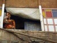 An Iraqi woman watches US Army soldiers from a balcony looking over a Baghdad street 22 May 2003. The US army was summoned by prostitutes living in the building after a firefight between prostitutes and gang members erupted over stolen merchandise.
