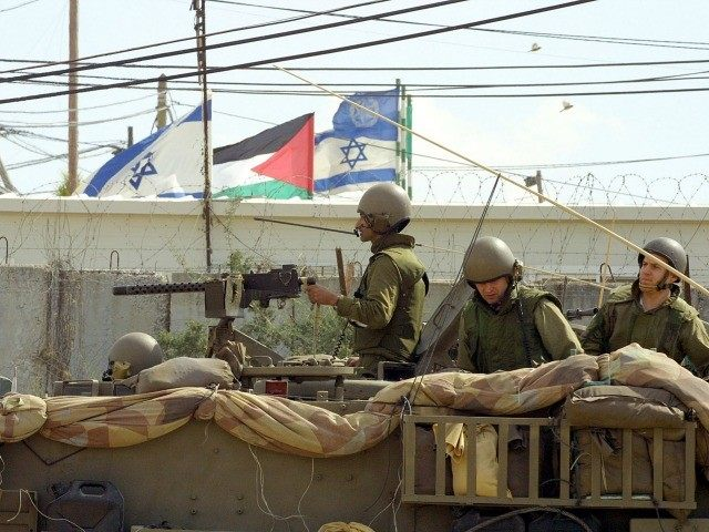 With a Palestinian flag to his back an Israeli soldier rides in an armored personnel carrier April 1, 2002 in the outskirts of the West Bank town of Qalqilia. I
