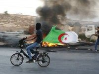 A Palestinian youth carries an Algerian flag as he rides a bicycle during clashes between Palestinian protesters and Israeli security forces near the Beit El settlement on the outskirts of Ramallah in the West Bank, on October 14, 2015