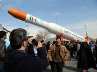 Iranians take pictures of the Simorgh (Phoenix) satellite rocket during celebrations in Tehran to mark the 37th anniversary of the Islamic revolution on February 11, 2016. Iranians waved 'Death to America' banners and took selfies with a ballistic missile as they marked 37 years since the Islamic revolution, weeks after Iran finalised a nuclear deal with world powers. / AFP / ATTA KENARE (Photo credit should read ATTA KENARE/AFP/Getty Images)