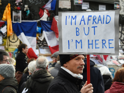 A man holding a placard reading 'I am afraid but I am here' during a gathering on Place de la Republique (Republic square) on January 10, 2016 in Paris, as the city marks a year since 1.6 million people thronged the French capital in a show of unity after attacks …