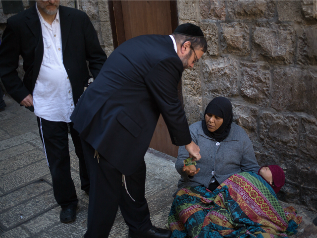 An ultra-orthodox man gives money to a Palestinian street beggar during the Pesach (Passover) holiday in the Old City of Jerusalem on April 6, 2015.