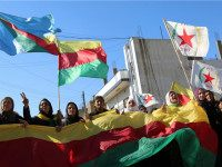 SYRIA, QAMISHLI : Kurdish women hold flags of the Kurdish People's Protection Units (YPG) political wing, the Democratic Union Party (PYD), and banners during a demonstration against the exclusion of Syrian-Kurds from the Geneva talks in the northeastern Syrian city of Qamishli on February 4, 2016. The talks in Geneva …