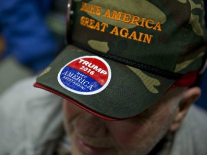Attendee Rich Travers wears a 'Make America Great Again' hat before Donald Trump, president and chief executive of Trump Organization Inc. and 2016 Republican presidential candidate, not pictured, speaks during a campaign rally at Pennichuck Middle School in Nashua, New Hampshire, U.S., on Monday, Dec. 28, 2015. Trump urged supporters …