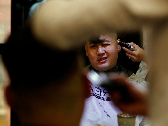 Australian Chinese Howard, 34, who does not disclose his last name, undergoes a haircut before turning into a North Korean leader Kim Jong-un lookalike at a hair salon in Hong Kong November 27, 2013. REUTERS/BOBBY YIP