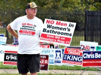 File - In this Oct. 21, 2015 file photo, a man urges people to vote against the Houston Equal Rights Ordinance outside an early voting center in Houston. On Tuesday, Nov. 3, 2015, voters statewide can give themselves tax breaks, pump billions of dollars into roads and make hunting and fishing constitutional rights by supporting seven amendments to the Texas Constitution on Tuesday's ballot. And Houston will choose a new mayor and decide whether to extend nondiscrimination protections to its gay and transgender residents in a referendum being watched nationally. (