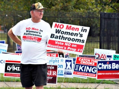 File - In this Oct. 21, 2015 file photo, a man urges people to vote against the Houston Equal Rights Ordinance outside an early voting center in Houston. On Tuesday, Nov. 3, 2015, voters statewide can give themselves tax breaks, pump billions of dollars into roads and make hunting and …