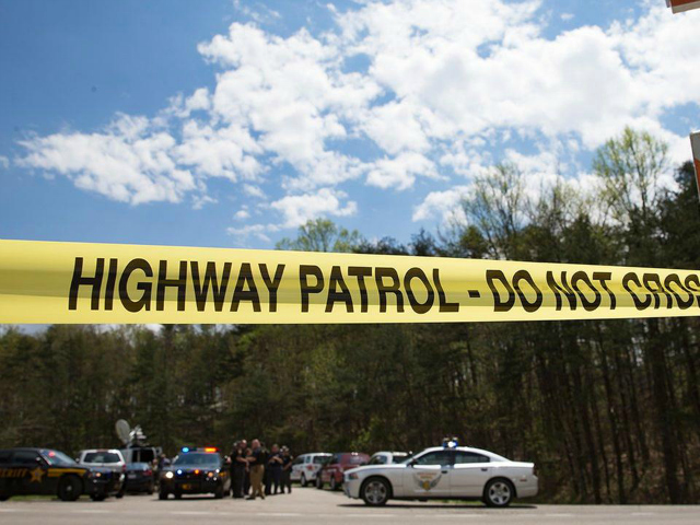 Police tape is deployed across from the Union Hill Road exit off Route 32 at a crime scene perimeter, Friday, April 22, 2016, in Pike County, Ohio. Shootings with multiple fatalities were reported along a road in rural Ohio on Friday morning, but details on the number of deaths and the whereabouts of the suspect or suspects weren't immediately clear. The attorney general's office said a dozen Bureau of Criminal Investigation agents had been called to Pike County, an economically struggling area in the Appalachian region some 80 miles east of Cincinnati. (AP Photo/John Minchillo)