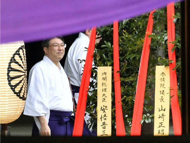 """Photo shows a """"masakaki"""" tree ritual offering (L) made by Prime Minister Shinzo Abe to the war-linked Yasukuni Shrine in Tokyo on April 21, 2016, at the start of its spring festival. China and South Korea, among other Asian nations, see the shrine as a symbol of Japan's past militarism …"""
