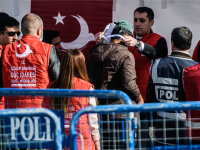 A Turkish officer registers a deported migrant from Greece after the arrival of a small Turkish ferry carrying migrants who are deported to Turkey, on April 4, 2016 at the port of Dikili district in Izmir.