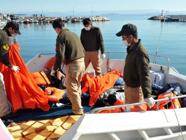 Turkisk coast guards prepare to remove the bodies of drowned migrants covered on the deck of a rescue boat, on February 8, 2016 at Altinoluk district, in Balikesir.
