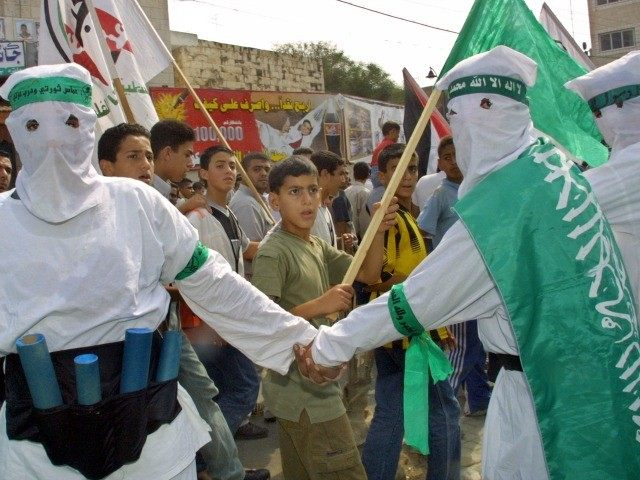 Masked Hamas militants, dressed as 'martyrs' for an honor guard while wearing mock ups of a suicide-bomber's 'belt of explosives' during the funeral of his slain leader Abdel Rahman Hamad October 14, 2001 in the West Bank town of Qalqilya, hours after the Islamic activist was gunned down by Israeli …