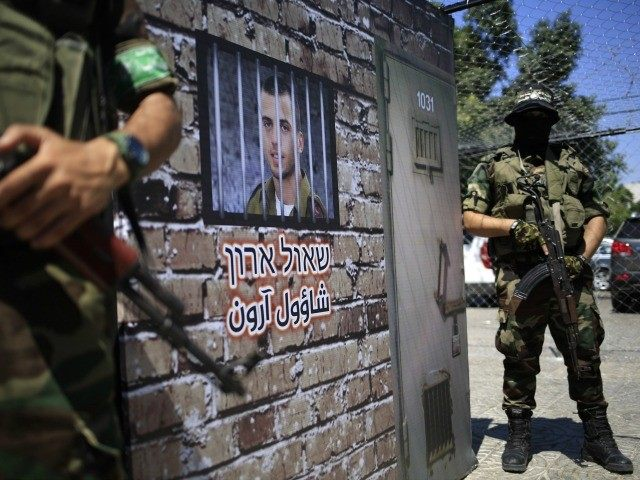 Members of the al-Qassam Brigades, Hamas' armed wing, stage a performance in which they stand guard outside a mural depicting a prison cell imitating where Israeli soldier Oron Shaul would have been held, during a presentation on September 2, 2015 at a main square in the centre of Gaza City.