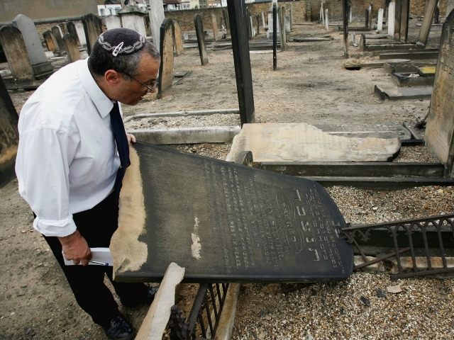LONDON - JUNE 16: A cemetary caretaker inspects the damage to Jewish gravestones in the East Ham Jewish cemetery, June 16, 2005, in London, England. Anti-Semitic vandals have desecrated gravestones and painted graffiti all over a old Jewish cemetery. (Photo by Graeme Robertson/Getty Images)