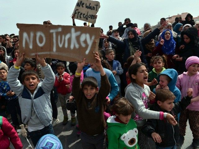 Refugees and migrants including children who left the Chios registration camp, shout slogans and hold placards reading ''No Turkey' during a protest on April 3, 2016 as they camp out in the port of Chios.