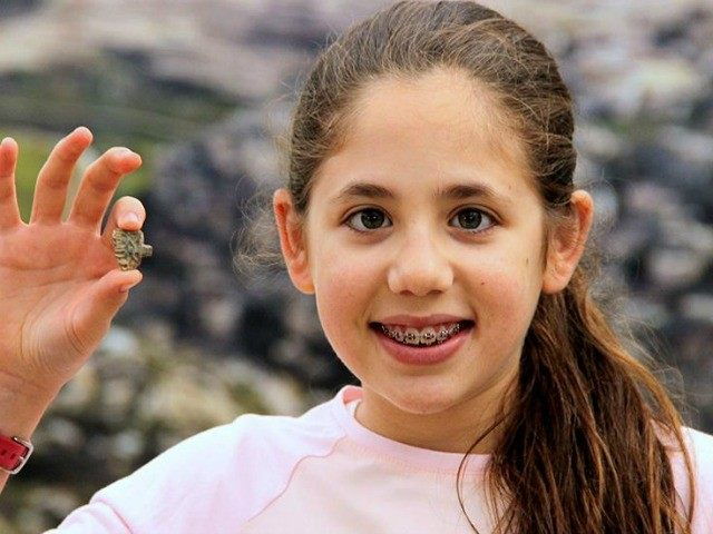 This image released by the Ir David Foundation - City of David on Tuesday, April 19, 2016 shows Neshama Spielman with an ancient Egyptian amulet dating back more than 3,200 years