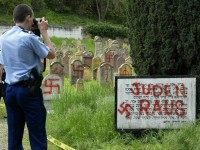 A French gendarme films, an anti-Semitic inscription written in German 'Jews Out' at a Jewish cemetery 30 April 2004 in Herrlisheim, in eastern France, where 127 graves have been desecrated.