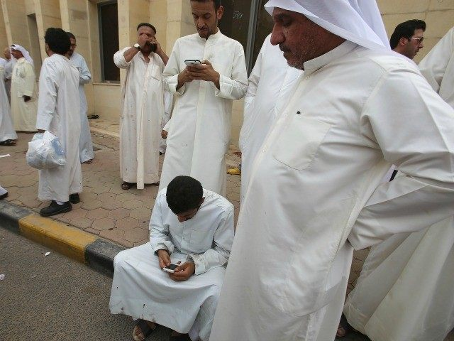 Kuwaiti men use smartphones as they gather outside the Shiite Al-Imam al-Sadeq mosque following a suicide bombing during Friday prayers on June 26, 2015, in Kuwait City.