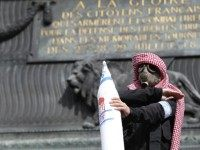 A protester wearing a gas mask and a kaffiyeh holds a fake rocket with the Israeli flag and swastikas as he performs the 'quenelle' gesture, popularised by a French controversial comedian and viewed as anti-semitic, on July 13, 2014 in Paris, during a demonstration against Israel and in support of …
