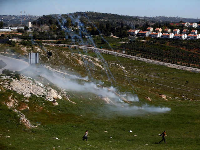 Palestinian protesters walk away amidst tear gas smoke during clashes with Israeli security forces following a march against Palestinian land confiscation on April 1, 2016 in the West Bank village of Nabi Saleh near Ramallah.