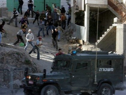 Palestinian youths throw stones at Israeli border police during clashes after Friday prayers in the West Bank city of Hebron on January 30, 2009.