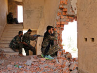 Kurdish People's Protection Units (YPG) fighters take up positions inside a damaged building in al-Vilat al-Homor neighborhood in Hasaka city, as they monitor the movements of Islamic State fighters who are stationed in Ghwayran neighborhood in Hasaka city, Syria July 22,... REUTERS/RODI SAID