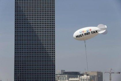 A blimp reading ''Google must pay tax'' is seen floating over the Tel Aviv skyline April 3, 2016.
