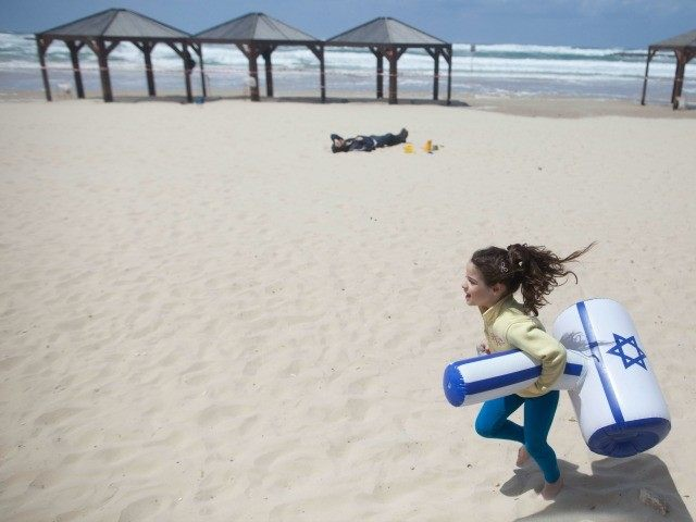 girl carrying a plastic hammer with the colors of the Israeli flag runs on a beach near the Mediterranean sea after a military air show marking the 67th anniversary of Israel's independence on April 23, 2015 in Tel Aviv, Israel.