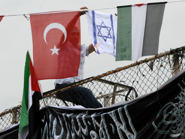 A demonstrator burns an Israeli flag as he sits between Turkish (L) and Palestinian flags during a protest against Israel on June 5, 2010 at Caglayan Square in Istanbu
