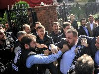 Riot police, left, force their way through a gate to enter the headquarters of opposition television stations and newspapers in Istanbul, Turkey, Wednesday, Oct. 28, 2017. Police in Istanbul have carried out a dawn raid, using tear gas to enter the headquarters of a media company linked to a government …