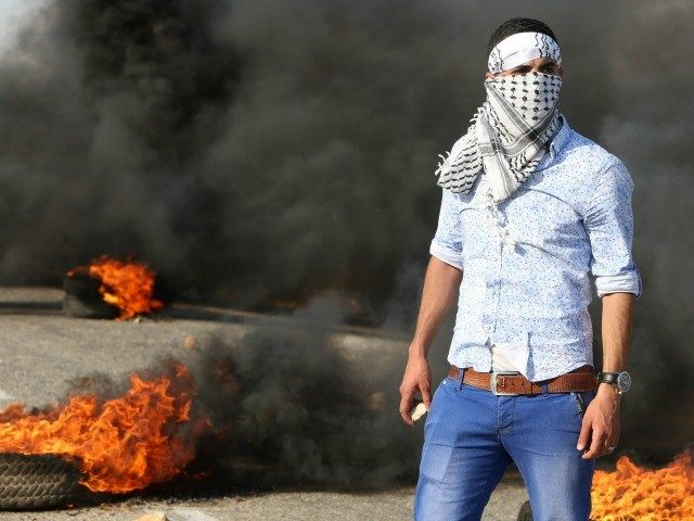 A Palestinian protester stands amid burning tires during clashes with Israeli security forces on a street leading to Duma village, on August 1, 2015, following a demonstration in reaction to the death of a Palestinian toddler burnt to death in an arson attack by suspected Jewish settlers in the West …