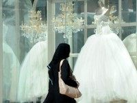 A Saudi woman walks past wedding dresses displayed in a shop window on February 4, 2013 at a mall in the Saudi capital Riyadh.