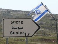 An Israeli flag flies near a sign indicating the way to the Palestinian village of Susya, south-east of Hebron, in the Israeli-occupied West Bank, on February 10, 2016.