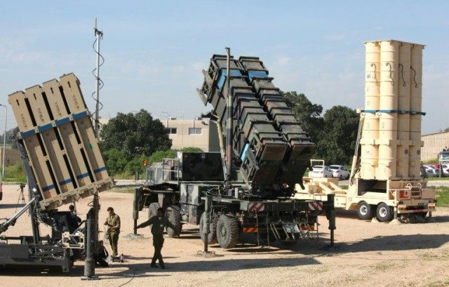 Israeli soldiers walk near an Israeli Irone Dome defence system (L), a surface-to-air missile (SAM) system, the MIM-104 Patriot (C), and an anti-ballistic missile the Arrow 3 (R) on February 25, 2016