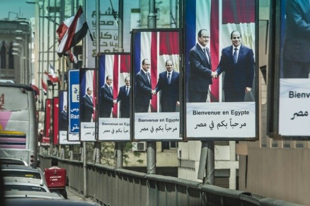 Posters in Cairo show Egypt's President Abdel Fattah al-Sisi (R) and his French counterpart Francois Hollande on April 17, 2016, ahead of the visit of the French president in the capital
