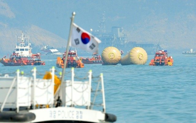 Rescue teams take part in recovery operations at the site of the sunken Sewol ferry, marked with buoys, off the coast of the South Korean island of Jindo on April 23, 2014