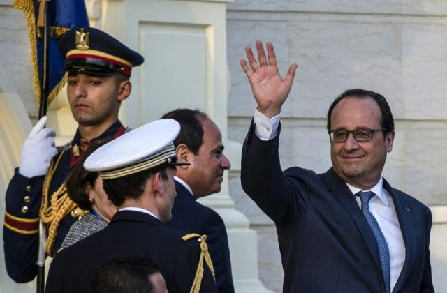 French President Francois Hollande (R) waves next to Egyptian counterpart Abdelfattah al-Sisi (C) after reviewing the honour guard during a welcome ceremony at the al-Quba presidential palace in Cairo on April 17, 2016