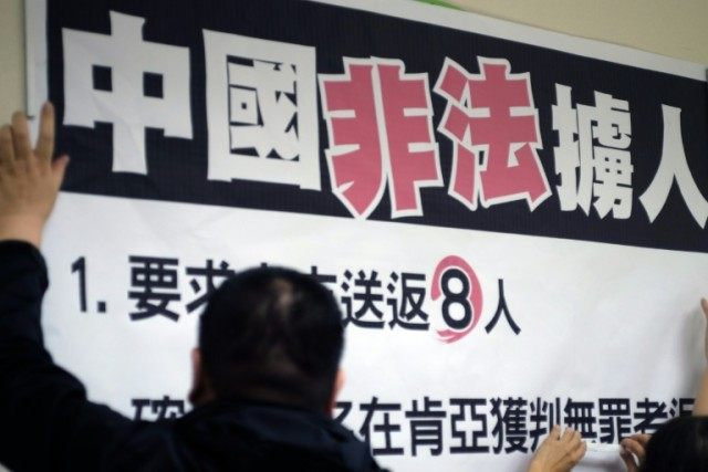 "Workers paste a sign reading ""China illegally abducts Taiwanese people"" during a press conference organised by lawmakers from the Democratic Progressive Party in Taipei on April 12, 2016"