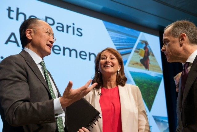 Jim Yong Kim, president of the World Bank Group (L), chats with Segolene Royal, Minister of Ecology, Sustainable Development and Energy of France and Mark Carney, Governor of the Bank of England, in Washington, DC, on April 14, 2016