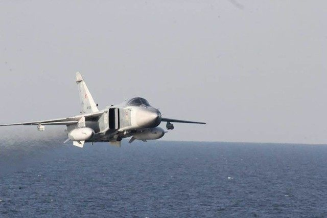 A Russian Su-24 warplane flies over the USS Donald Cook in the Baltic Sea