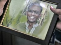 A man holds a portrait of Bangladeshi professor Rezaul Karim Siddique, who was hacked to death by unidentified attackers in Rajshahi on April 23, 2016