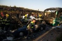 Israeli firemen and emergency services gather around the remains of a burnt-out a bus and car in Jerusalem on April 18, 2016
